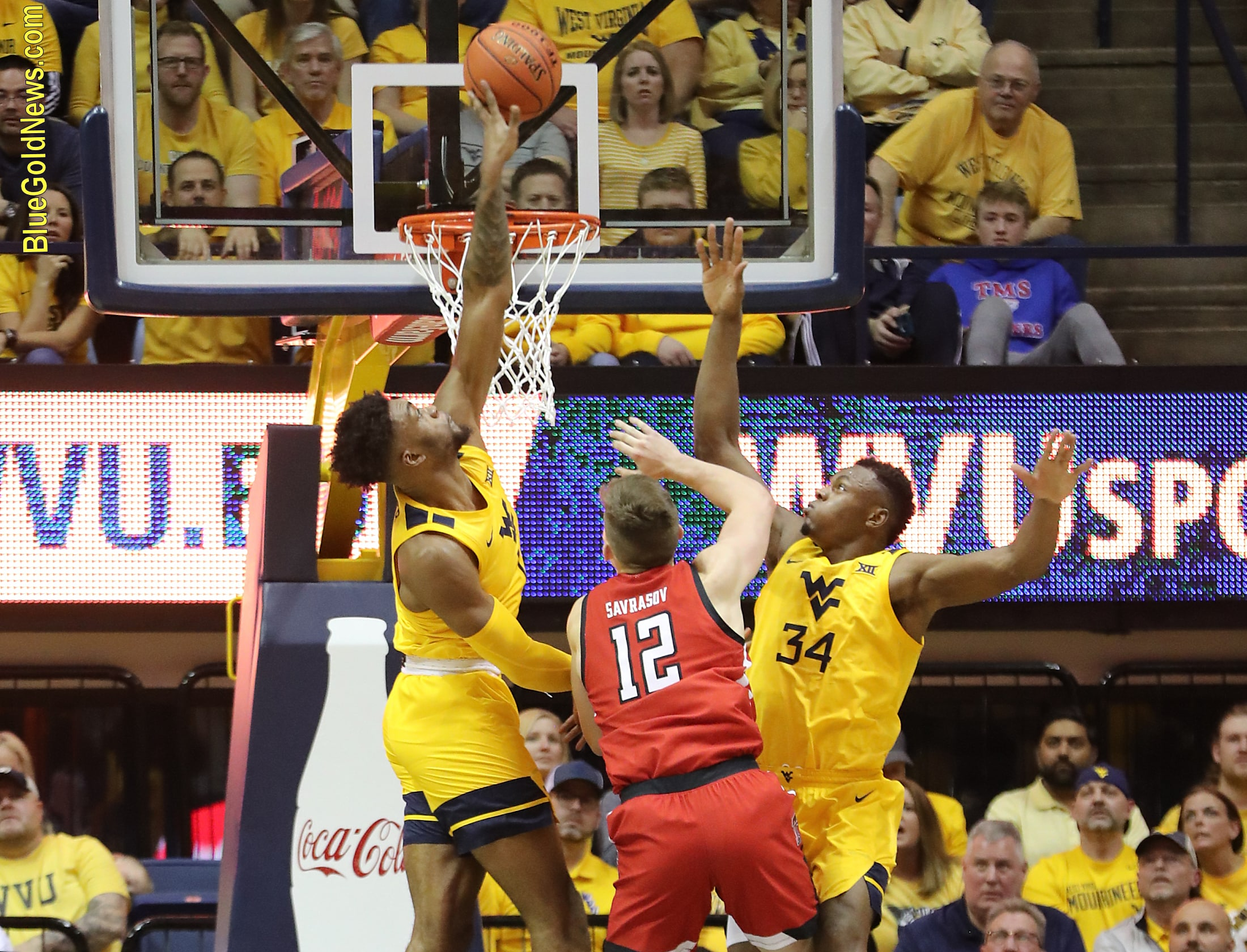 West Virginia forward Derek Culver (10 blocks the shot of Texas Tech's Andrei Savrasov (12) in front of the rim