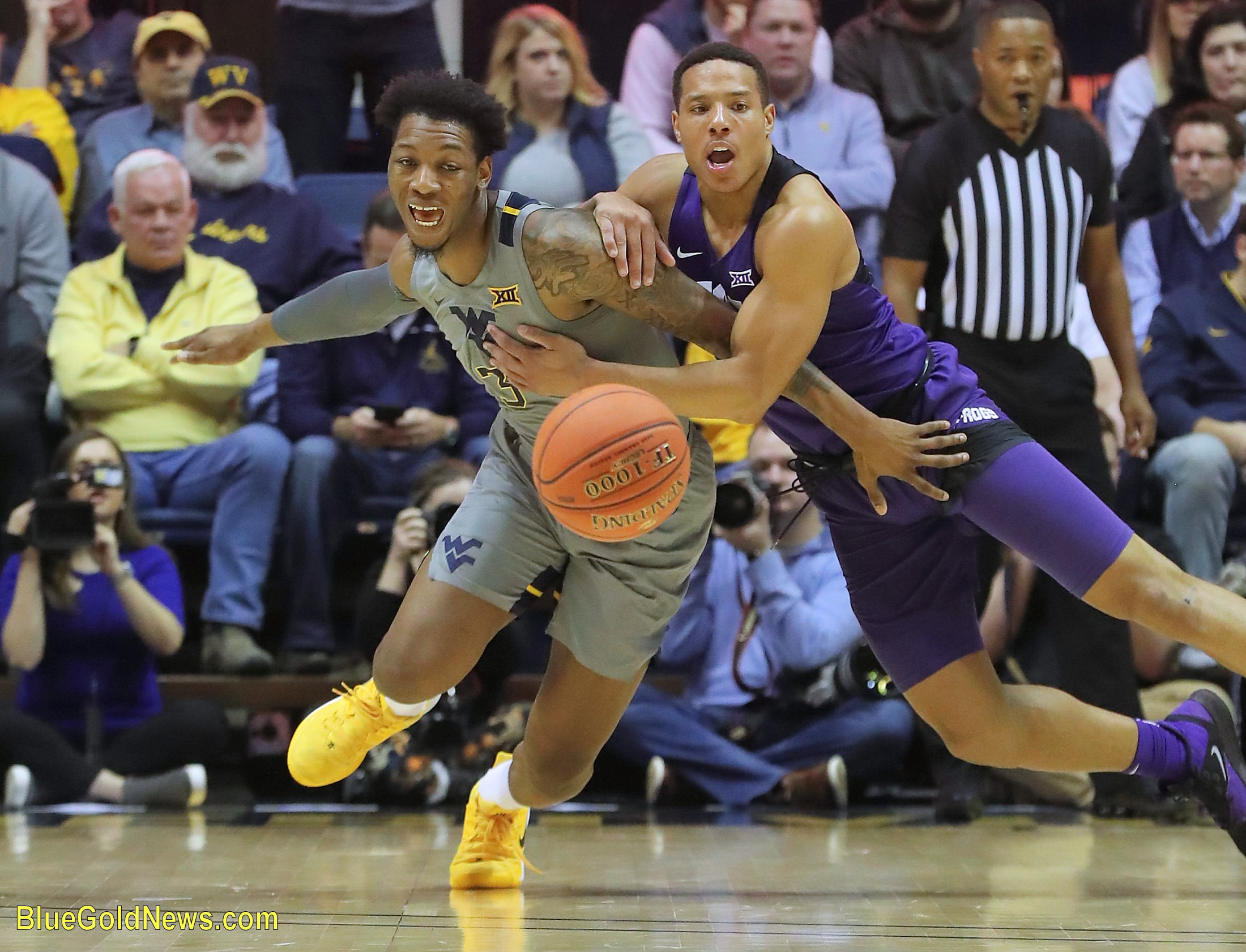 West Virginia's Gabe Osabuohien (3) is held by TCU's Desmond Bane while chasing a loose ball