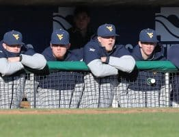 Railbirds: West Virginia players line the dugout railing to watch the action