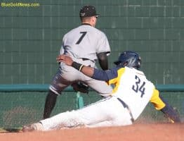 West Virginia catcher Paul McIntosh (34) slides into third ahead of a throw