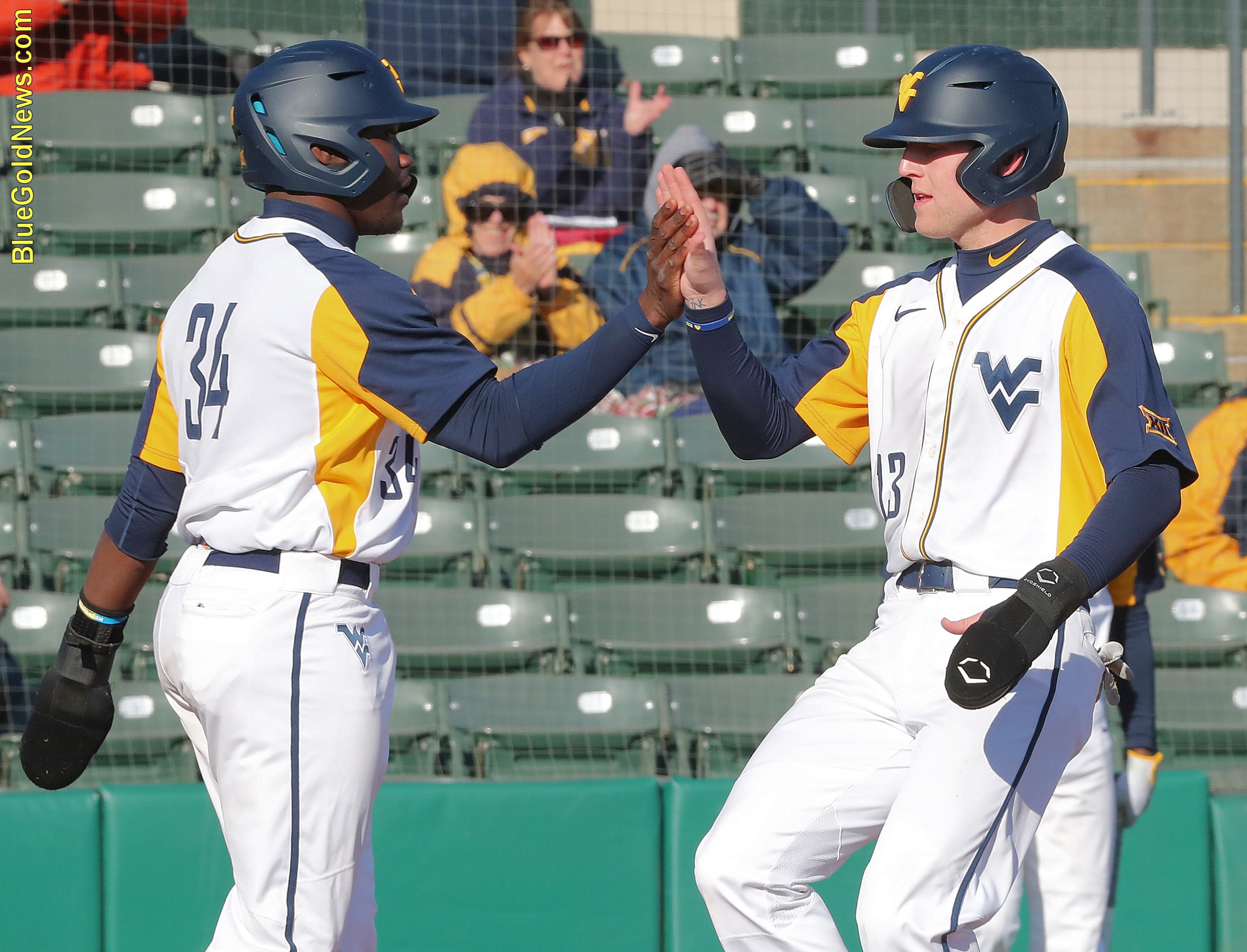 West Virginia catcher Paul McIntosh (34) greets Kevin Brophy (13) at the plate