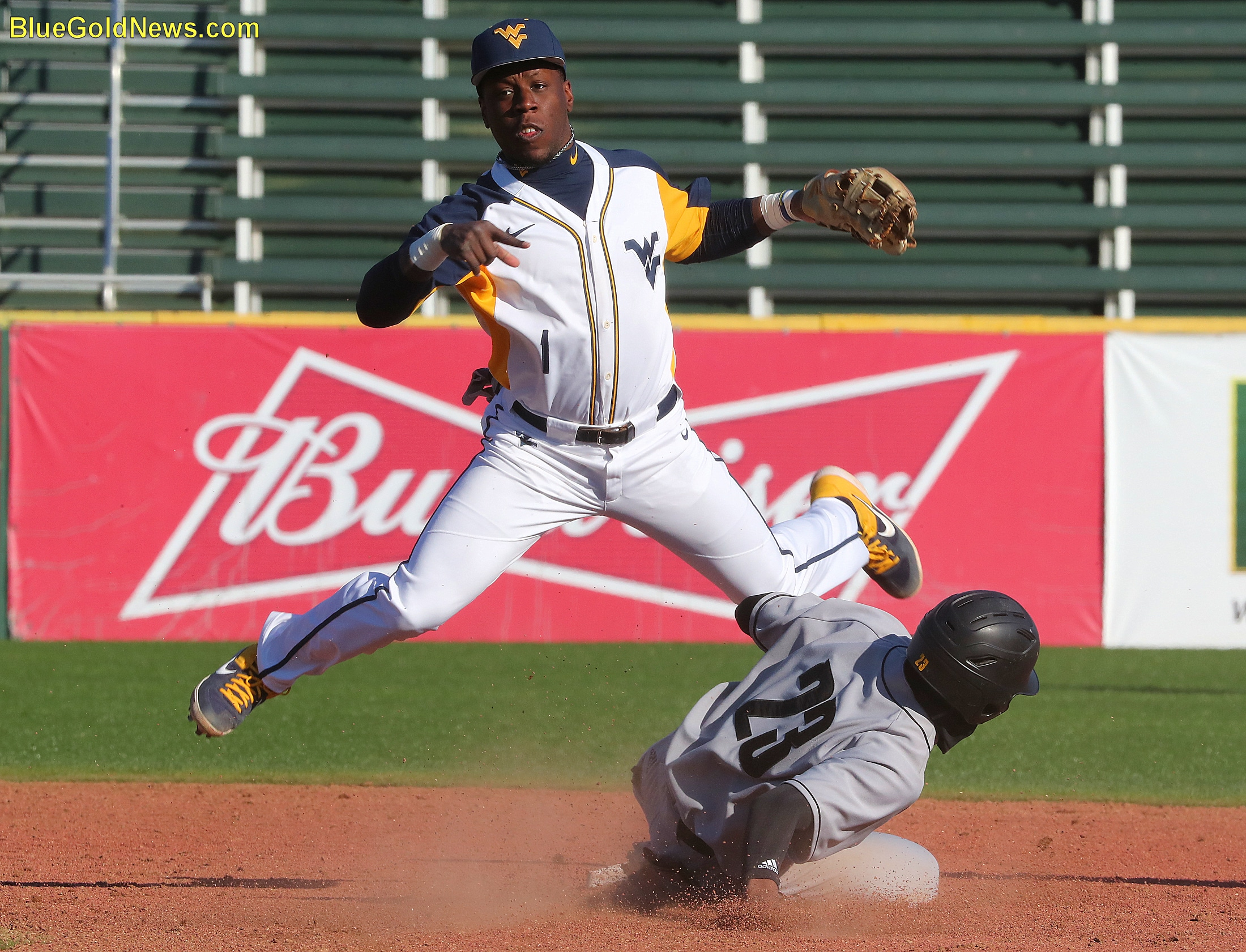 West Virginia infielder Tyler Doanes (1) avoids the slide of Kennesaw State's Nick Hassan (23) to complete a double play