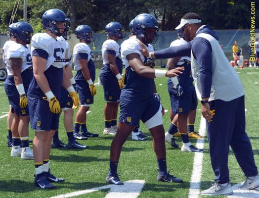 West Virginia graduate assistant Julian Miller (right) demostrates a technique to Tavis Lee (88)