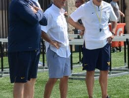 West Virginia head coach Neal Brown (right) visits with Tommy Bowden (center)