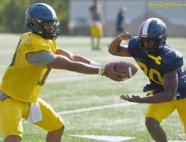 West Virginia quarterback Trey Lowe (10) hands off to running back Alec Sinkfield
