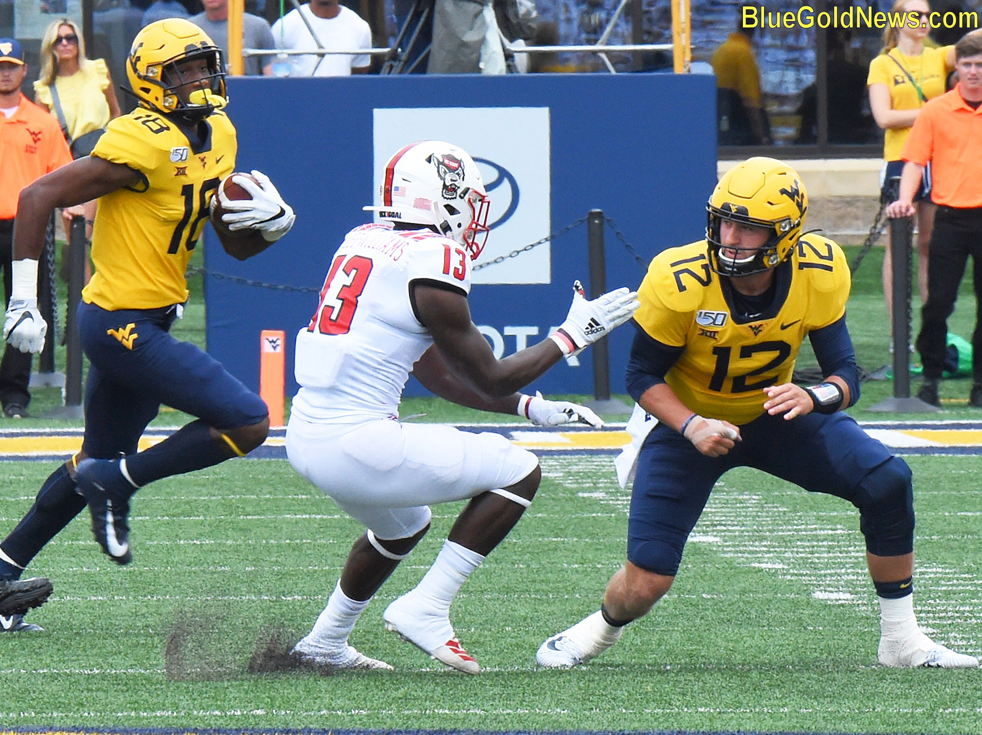 West Virginia quarterback Austin Kendall (12) prepares to throw a block on N.C. State's Tyler Baker-Williams (13)