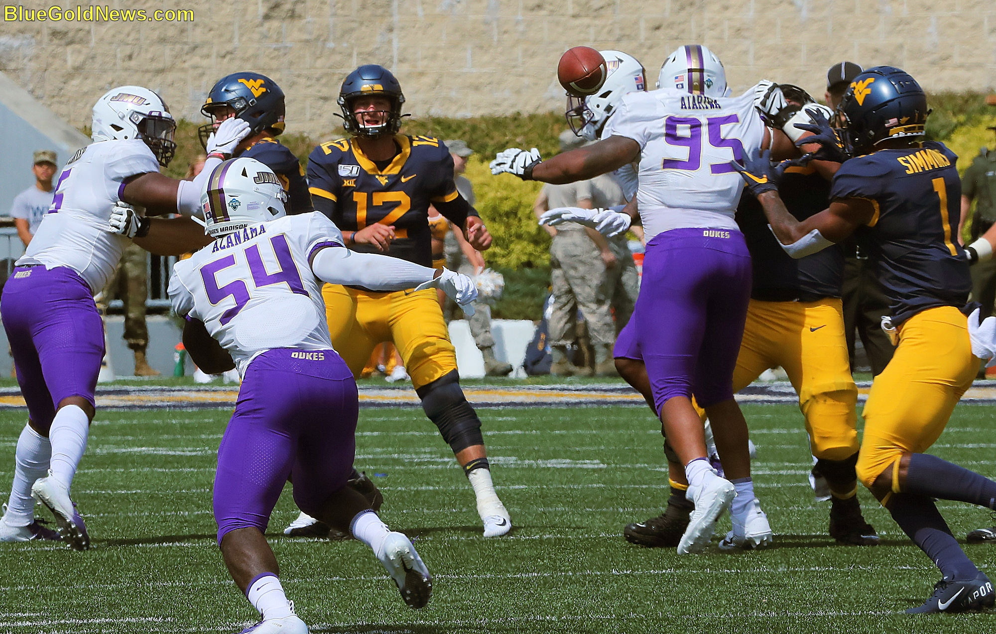 West Virginia quarterback Austin Kendall (12) threads the needle with a pass to T.J. Simmons (1)