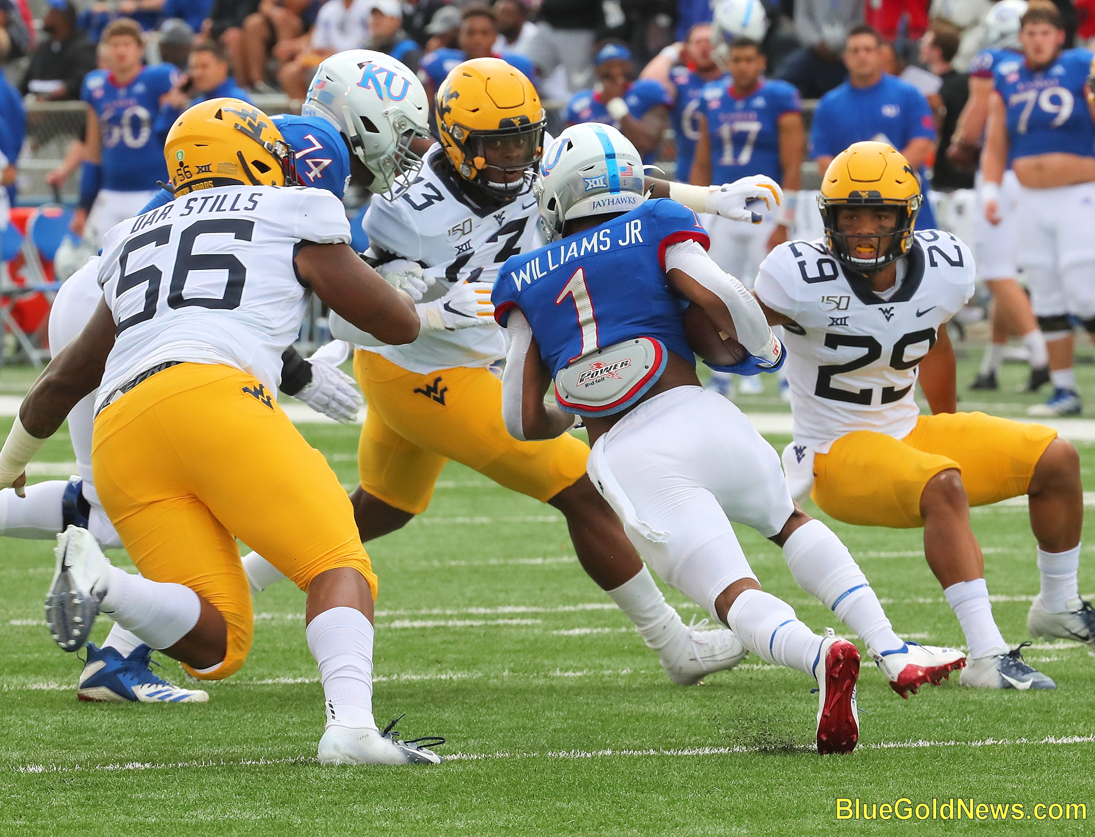 West Virginia defenders Darius Stills (56), Jeffery Pooler (13) and Sean Mahone (29) close in on Kansas' Pooka Williams (1)