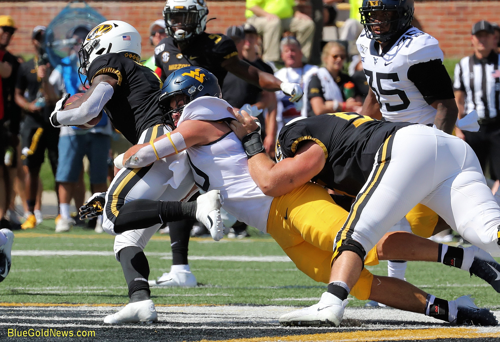 West Virginia linebacker Dylan Tonkery (ceter) holds on for a tackle while being held from behind