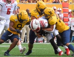 West Virginia defenders JoVanni Stewart (9) Dylan Tonkery (10) and Sean Mahone (29) converge on N.C. State's Emeka Emezie (3)