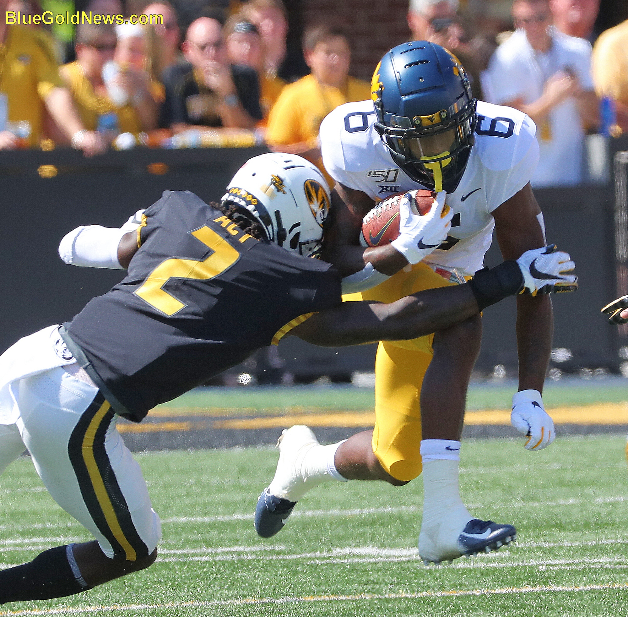 West Virginia running back Kennedy McKoy (6) tries to skip away from the tackle attempt of Missour's DeMarkus Acy (2)
