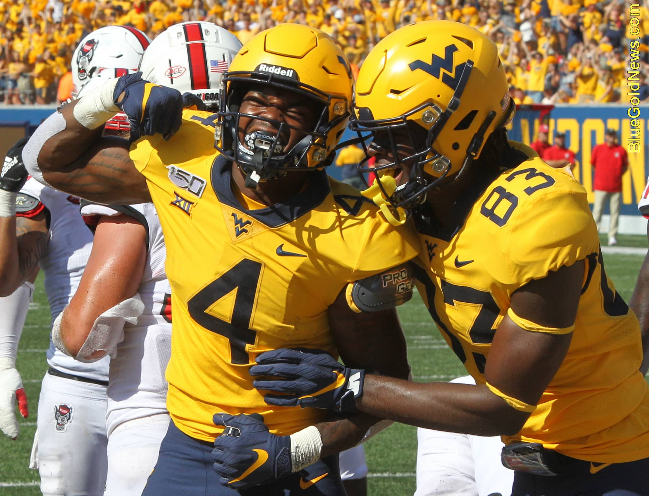 West Virginia running back Leddie Brown (4) celebrates his first touchdown of 2019 along with Bryce Wheaton (83)