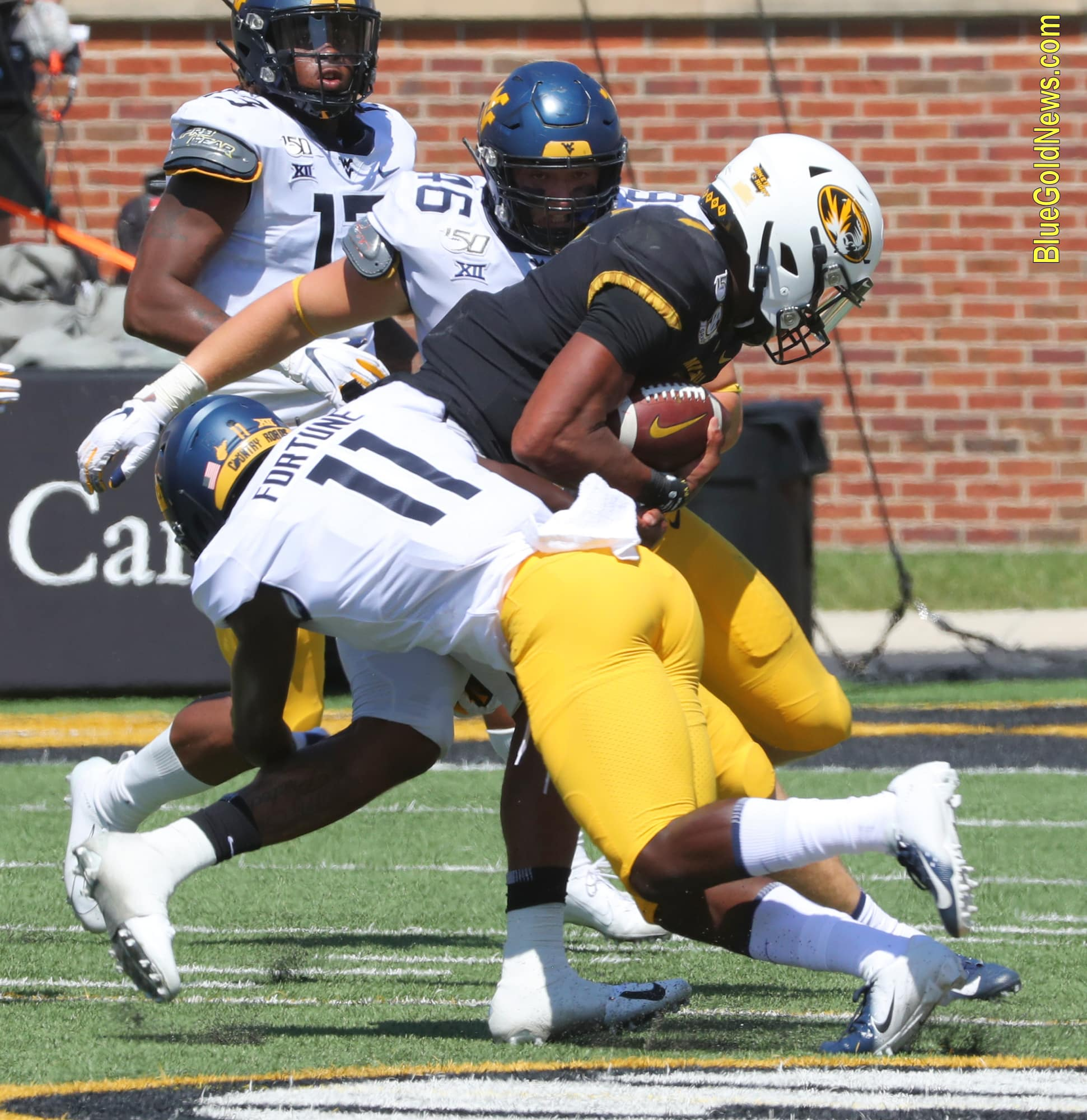West Virginia cornerback Nicktroy Fortune (11) makes a tackle while Reese Donahue (46) moves in to assist