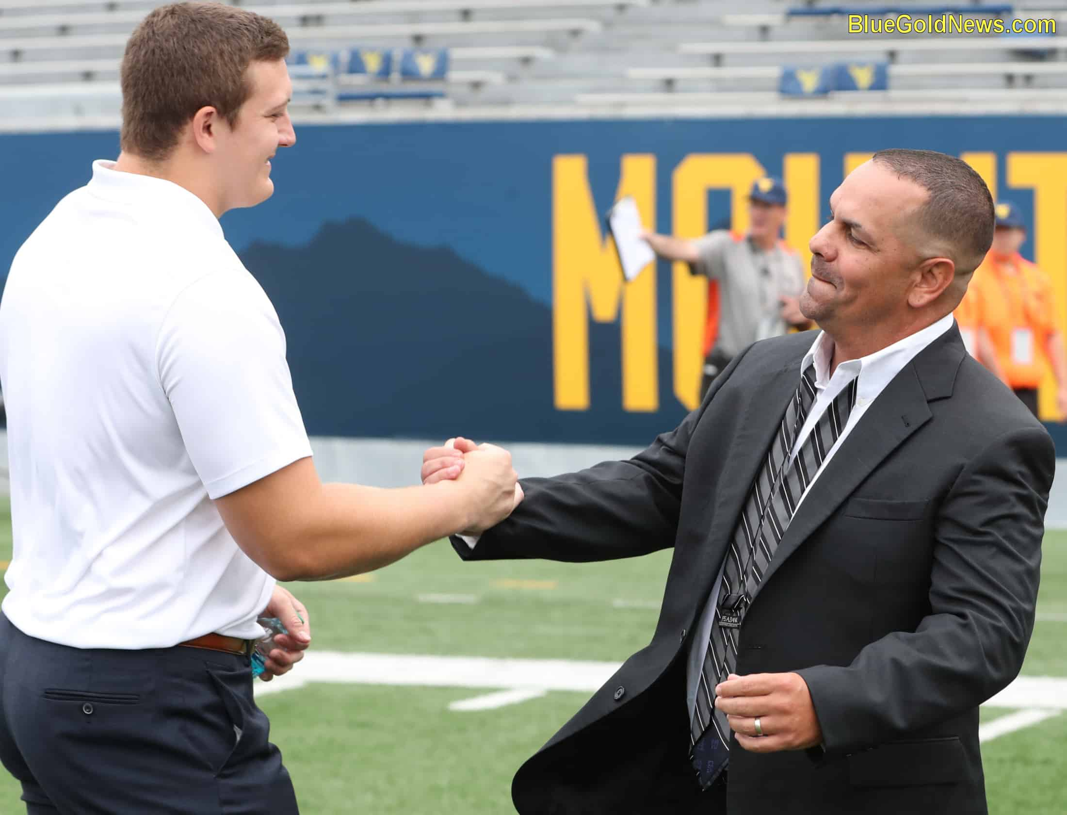 West Virginia defensive lineman Reese Donahue (l) greets N.C. State co-defensive coordinator Tony Gibson