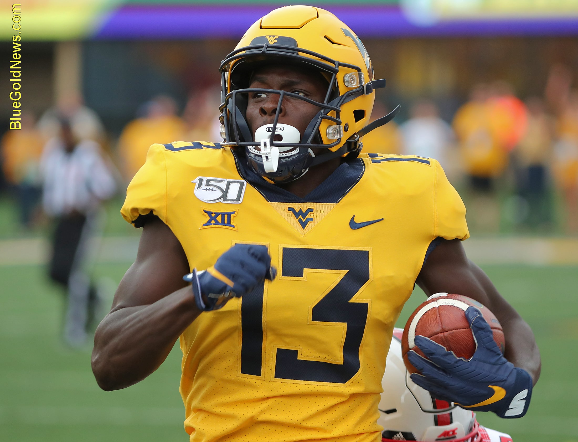 West Virginia receiver Sam James eyes the scoreboard to check his pursuers