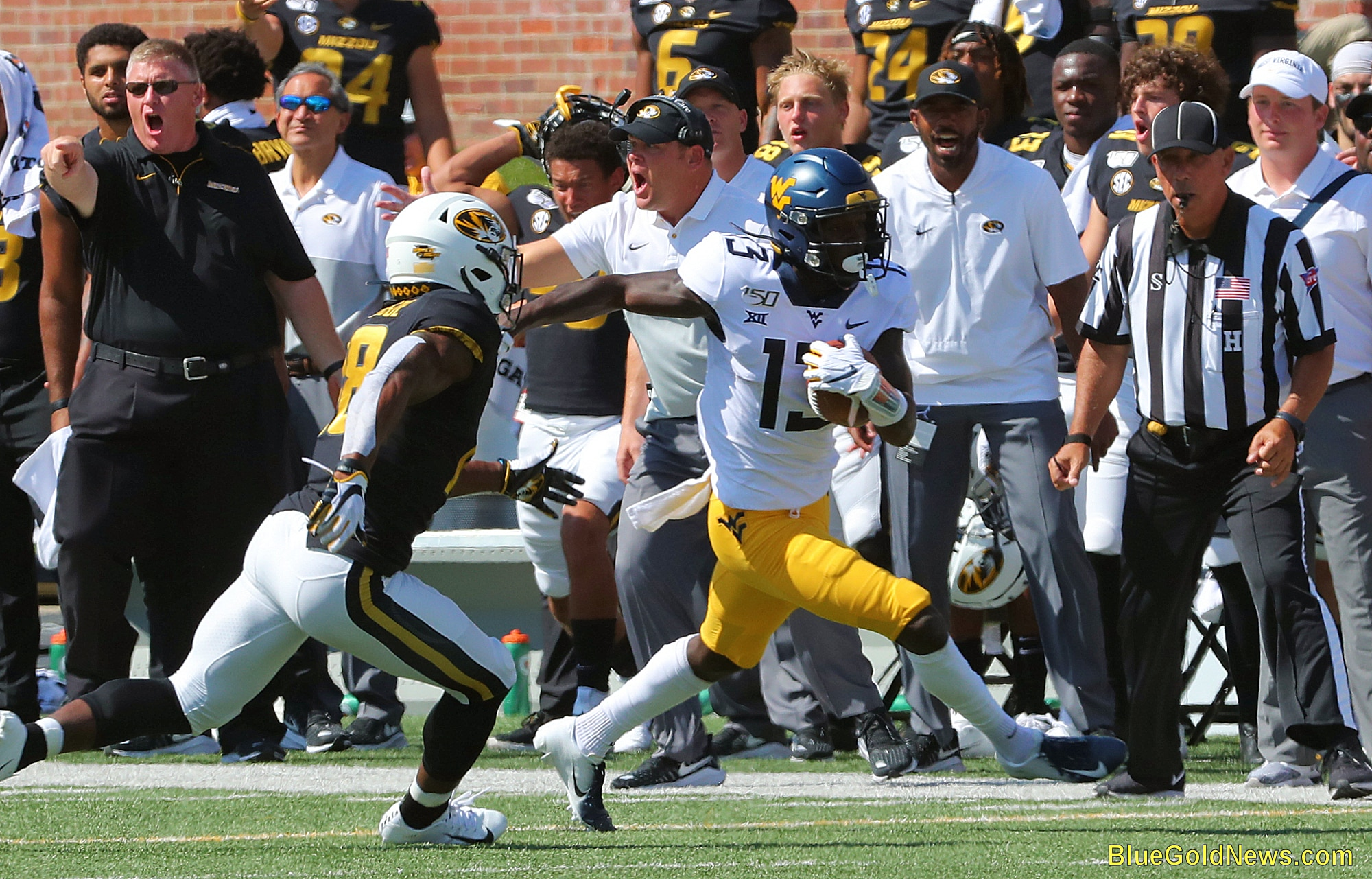 West Virginia wide receiver Sam James (13) gains yaradge as the Missouri sideline erupts in protest