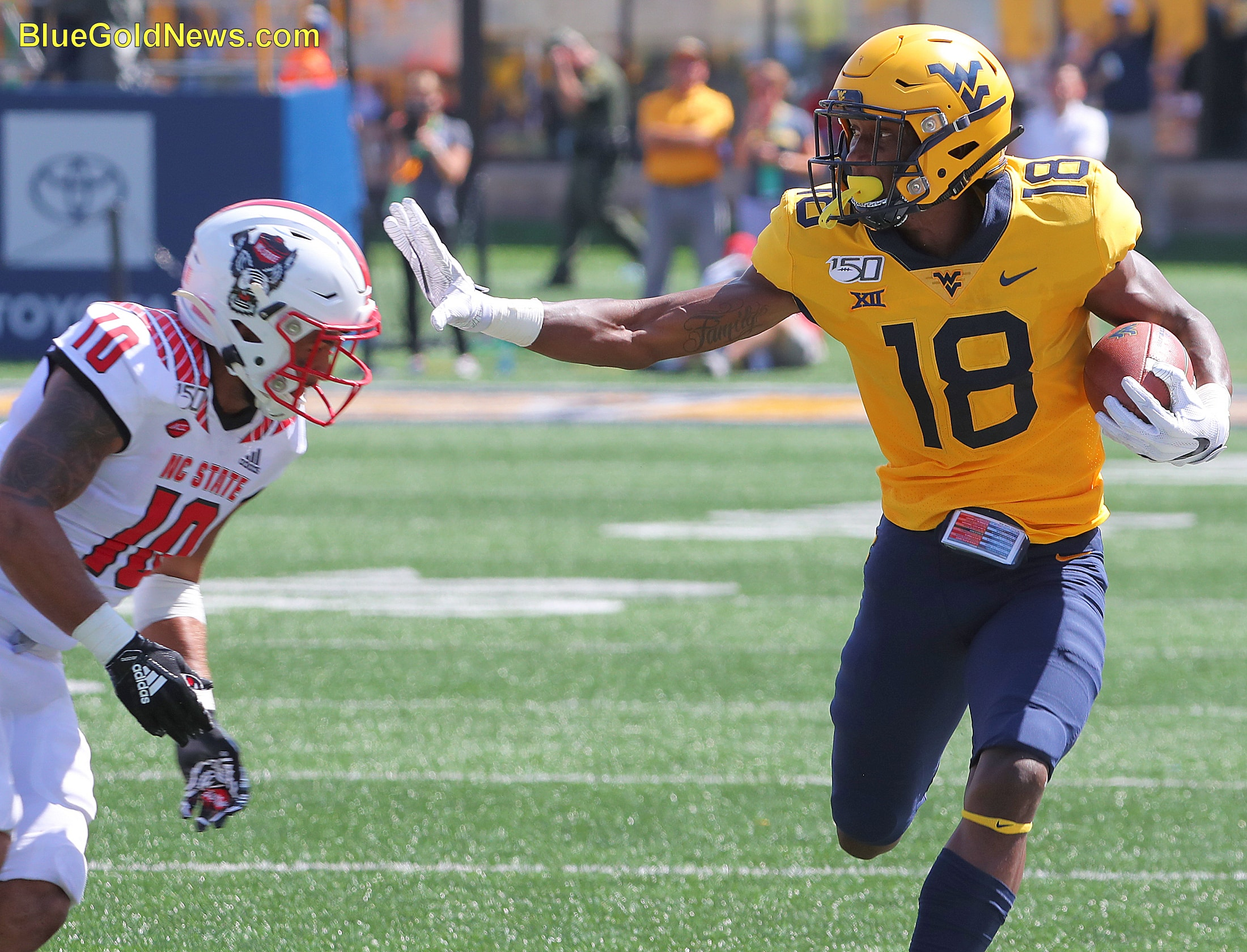 West Virginia wide receiver Sean Ryan (18) applies a stiff-arm to N.C. State's Tanner Hingle