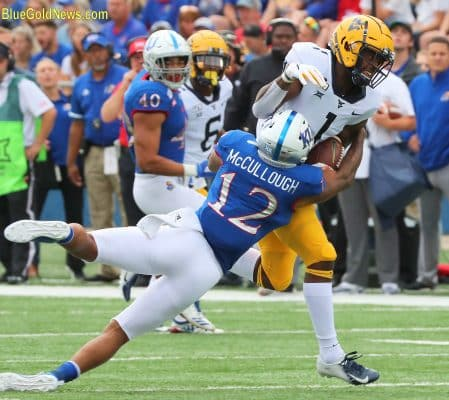 West Virginia wide receiver TJ Simmons (1) strains through the tackle attempt of Kansas' Jeremiah McCullough (12)