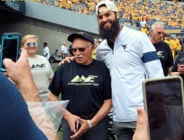 Cell phones click away as former West Virginia quarterback Will Grier meets some of the Mountain Eagles, members of a support group for wounded veterans