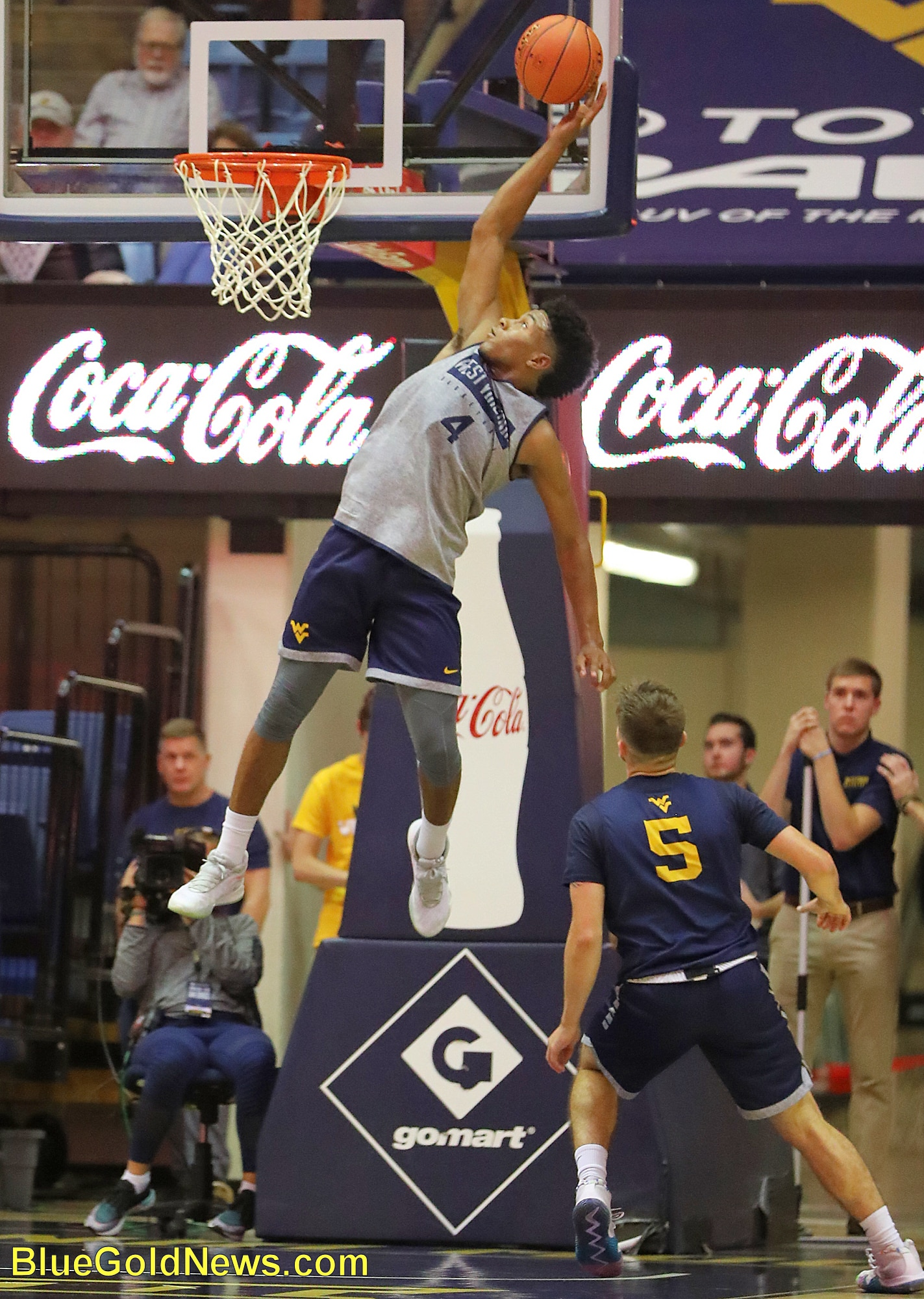 West Virginia guard Miles McBride (4) elevates for an alley-oop pass