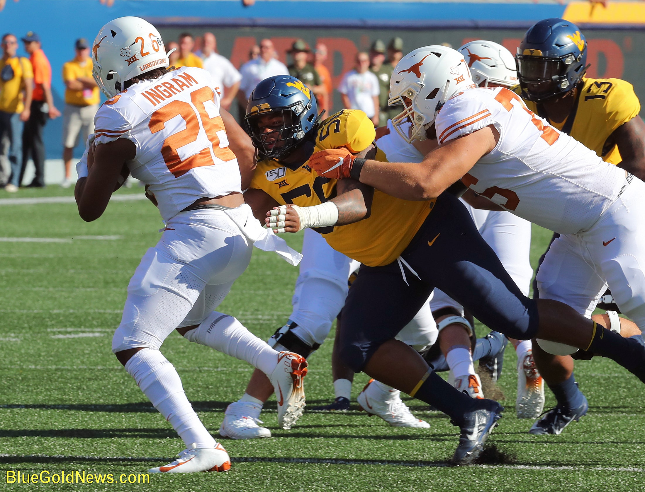 West Virginia defensive lineman Darius Stills (56) records a tackle for loss against Keaontay Ingram (26) despite the hold of Reese Moore (76)
