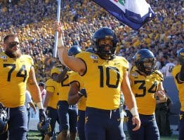West Virginia linebacker Dylan Tonkery (10) carries the state flag