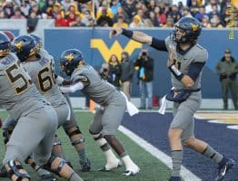 West Virginia quarterback Jack Allison gets good protection as he throws from his end zone