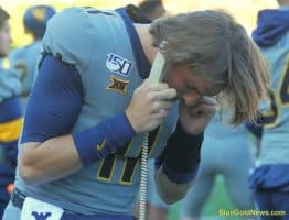 West Virginia quarterback Jack Allison communicates with coach Sean Reagan in the press box