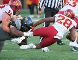 West Virginia defensive lineman Jordan Jefferson (left) makes a tackle on Iowa State's Breece Hall (28)