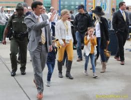 West Virginia head coach Neal Brown (waving) and family head into Milan Puskar Stadium
