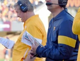 West Virginia head coach Neal Brown (right) looks at the scoreboard while defensive coordinator Vic Koenning (left) scans his play sheet