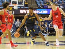 West Virginia forward Derek Culver (1) dribbles between a pair of Duquesne defenders