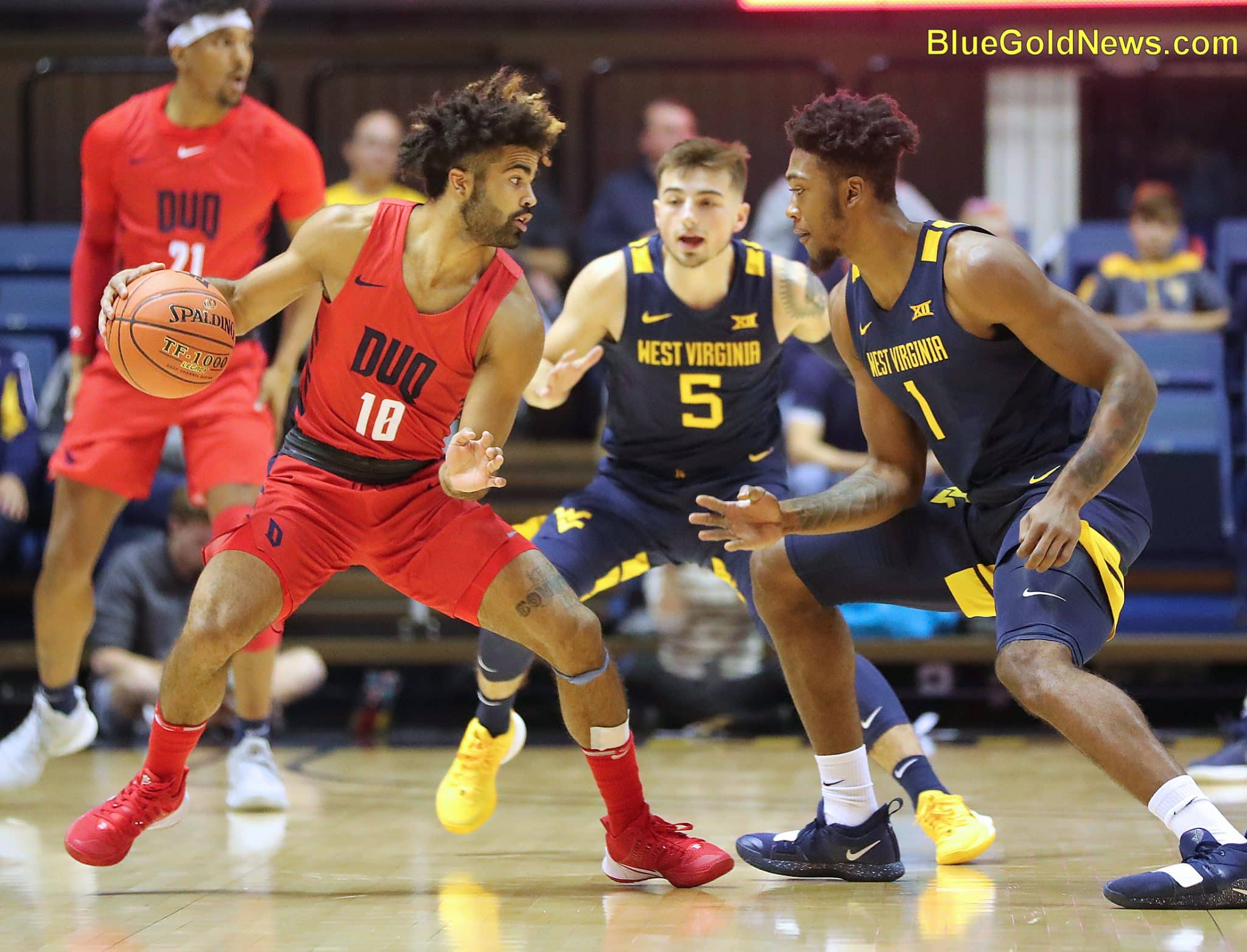 West Virginia forwrd Derek Culver (1) cuts off the floor as Jordan McCabe (5) moves up to trap Duquesne's Sincere Carry (10)