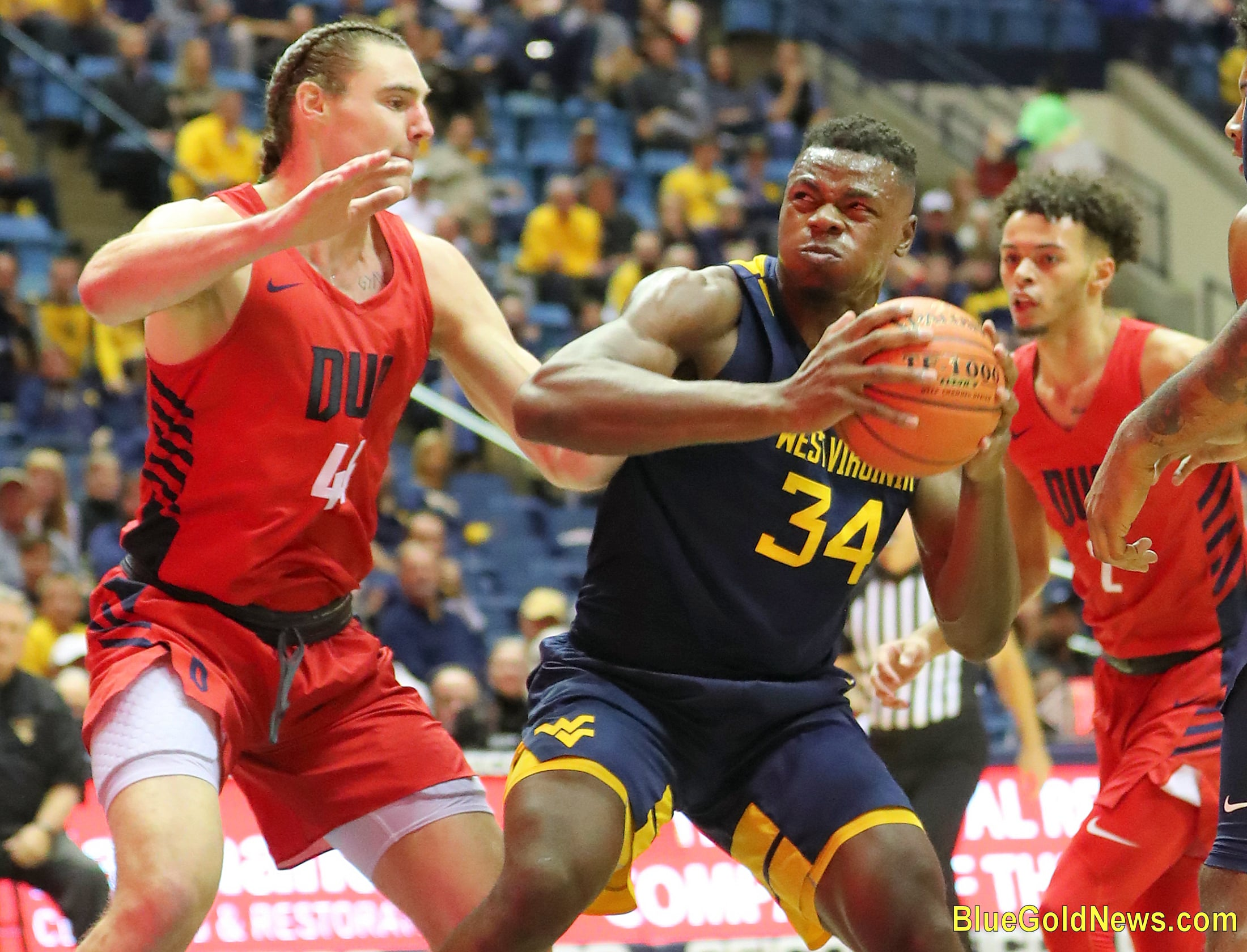 West Virginia forward Oscar Tshiebwe (34) clears space against Duquesne's Bailey Steele (44)