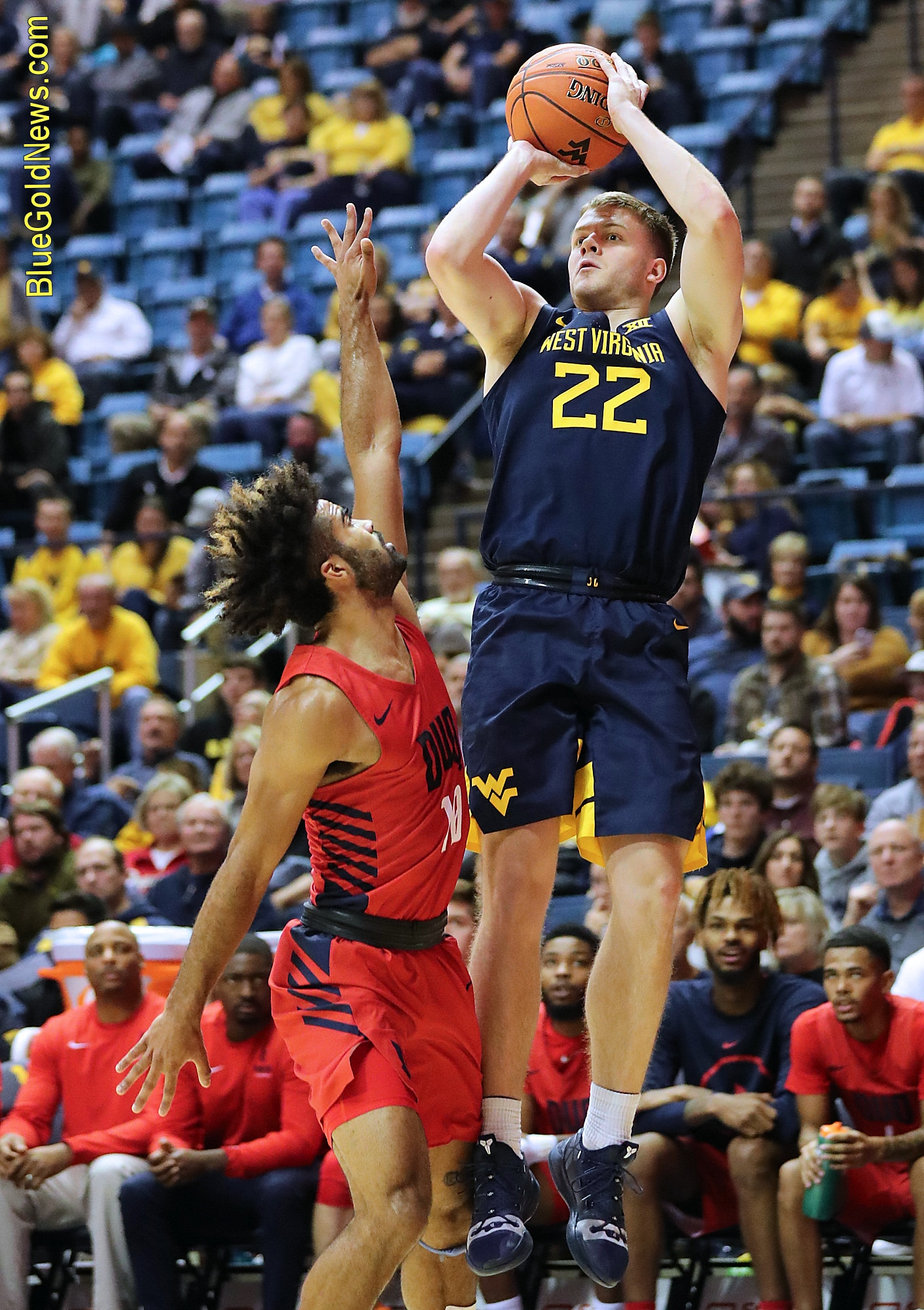 West Virginia guard Sean McNeil (22) eyes the basket on a jumper over Duquesne's Sincere Carry (10)