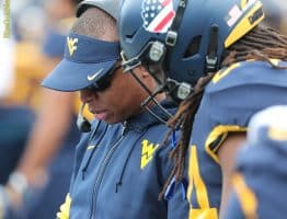 West Virginia running backs coach Chad Scott (left) reviews plays with freshman Tony Mathis