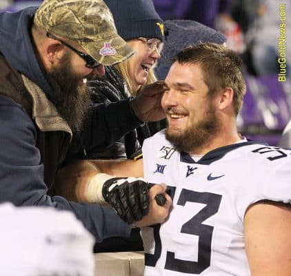 West Virginia offensive lineman Colton McKivitz greets his parents after WVU's win over Kansas State