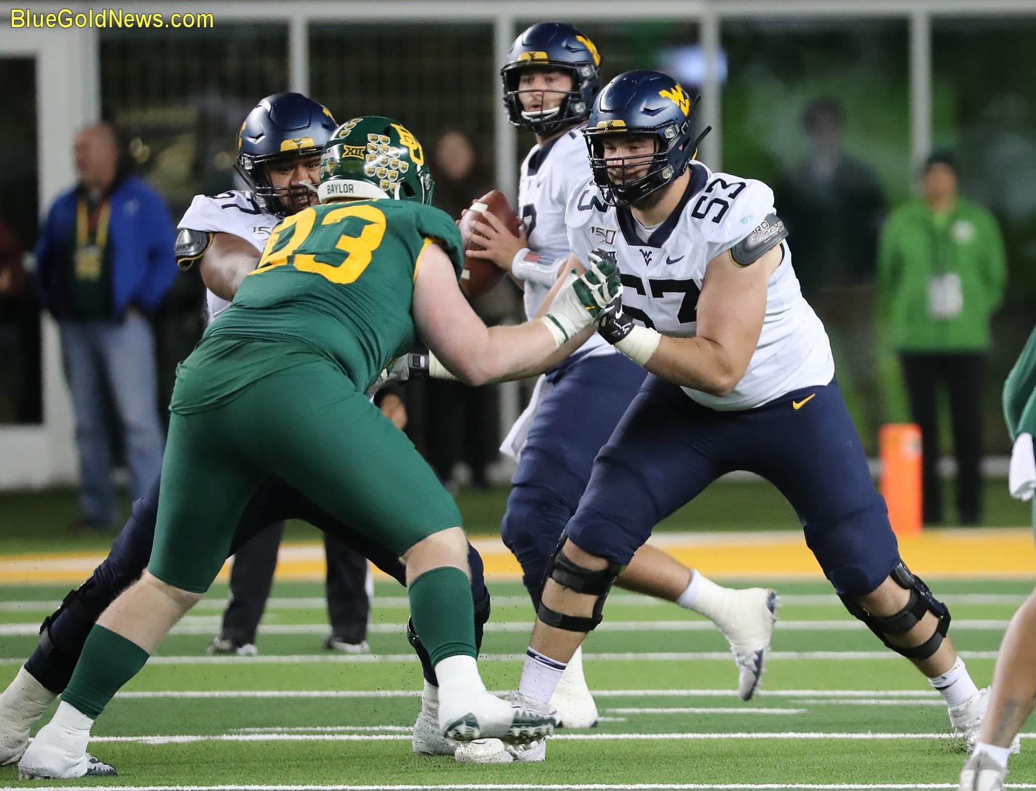 West Virginia offensive linemen Colton McKivitz (53) and Mike Brown (left) pass protect for quarterback Austin Kendall