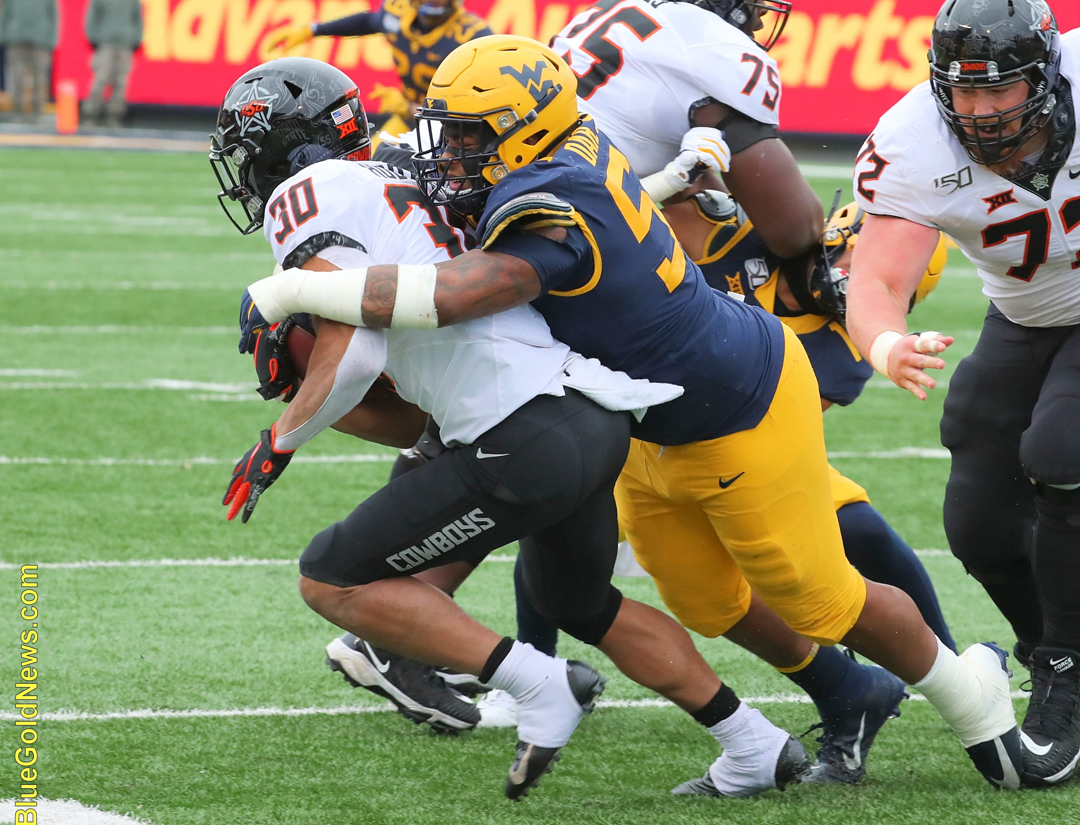West Virginia defensive lineman Darius Stills (56) wraps up Oklahoma State's Chuba Hubbard