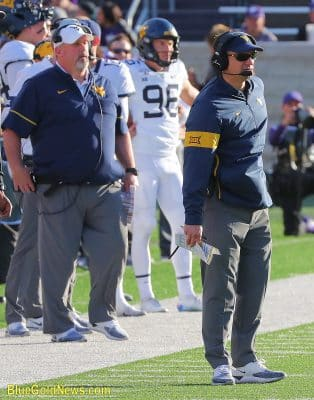 West Virginia head coach Neal Brown (right) tries to decipher the result of a play