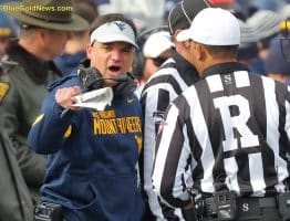 West Virginia head coach Neal Brown protests the lack of a pass interference call as referree Reggie Smith listens