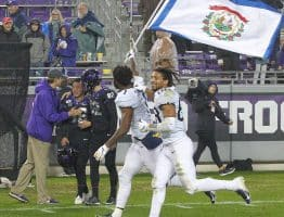 West Virginia receivers TJ Simmons (1) and Isaiah Esdale (88) lap the field with the state flag as TCU cornerback CJ Ceasar is consoled