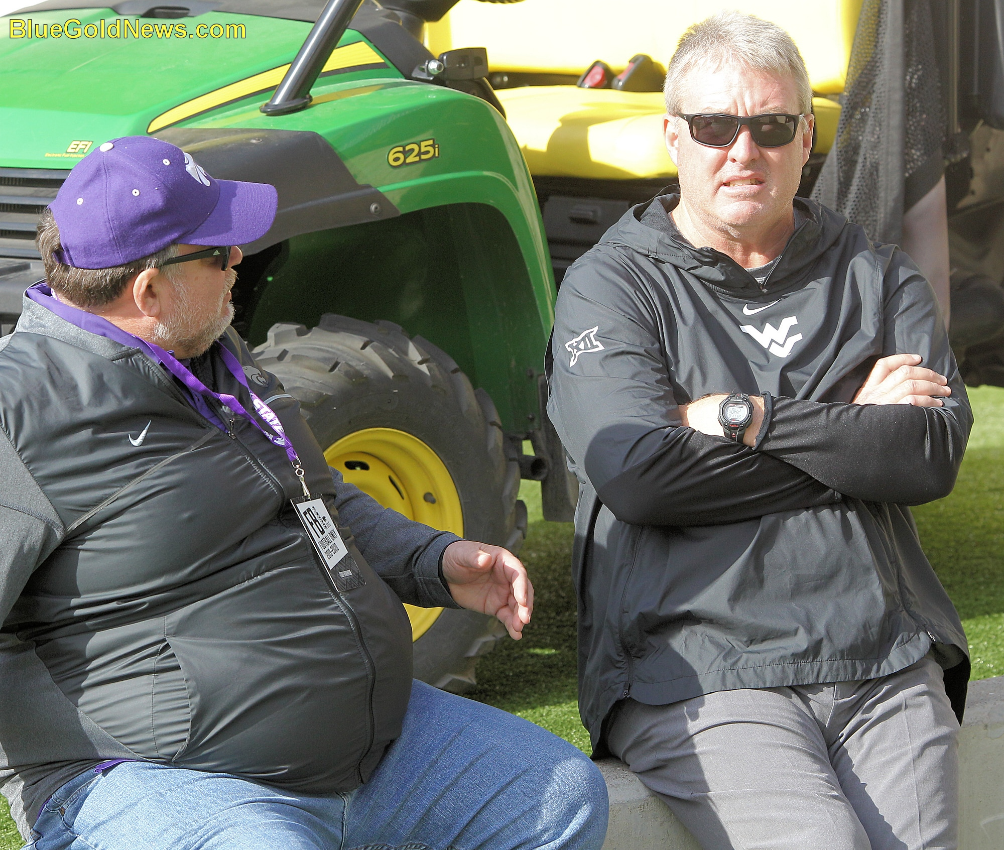 West Virginia assistant coach Vic Koenning (right) visits with a a K-State acquaintance