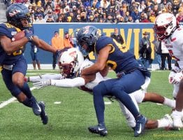 West Virginia receiver Winston Wright (16) is bottled up on a return