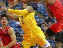 West Virginia guard Brandon Knapper takes a shot to the head from Austin Peay's Alec Woodard (22)