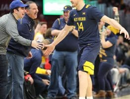 West Virginia guard Chase Harler celerates with fans courtside as the Mountaineers lock away a win over Ohio State