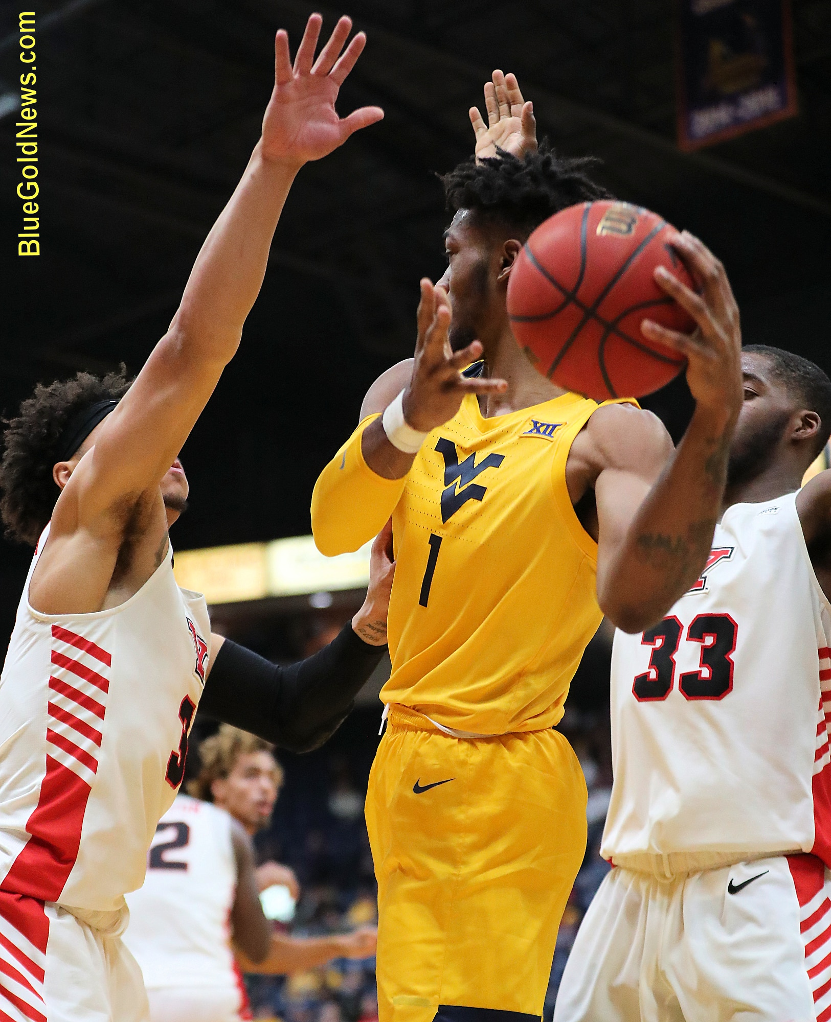 West Virginia forward Derek Culver (1) passes out of a Youngstown State doubleteam consisting of Darius Quisenberry (3) and Naz Bohannon (33)