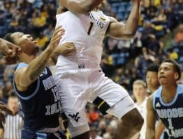 West Virginia forward Derek Culver (1) appears to be enjoying himself as he makes a move past Rhode Island's Dana Tate (12)