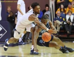 West Virginia forward Derek Culver (1) deflects the ball away from Rhode Island's Cyril Langevine (10)