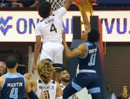 West Virginia guard Deuce McBride (4) goes high for a block attempt against Rhode Island's Jeff Downtin (11)